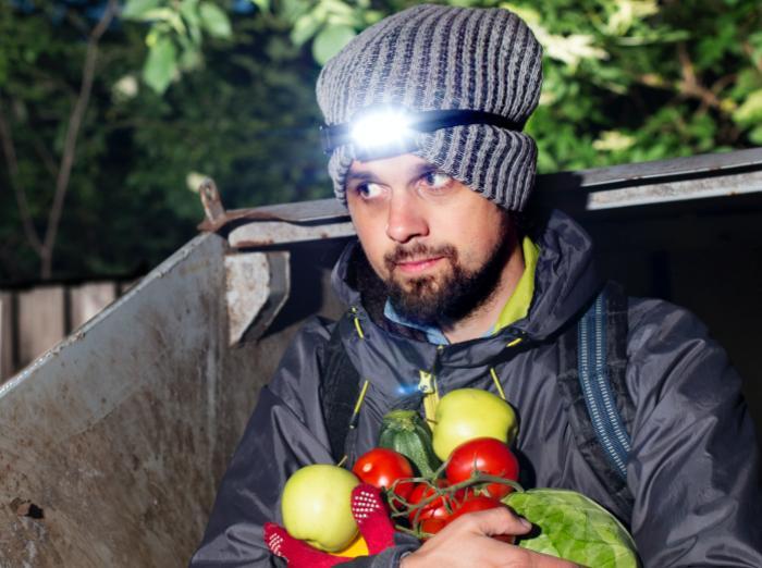 Andreas Jakobsson med frukt och grönt i famnen med pannlampan på reser sig ur en container